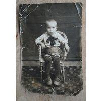 Фото мальчика в плетеном кресле. 1930-е. 9.5х14 см.