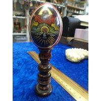 Яйцо с образами на деревянной подставке.