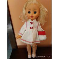 Кукла говорящая в белом пальто.