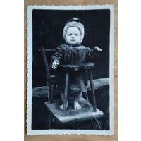Фото ребенка на стульчике для кормления. 1950-е. 6х8.5 см.